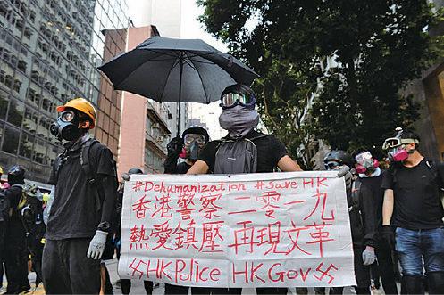 上周日,有抗爭者手持抗議港府縱容警方濫用暴力鎮壓的標語。(大紀元資料圖片)