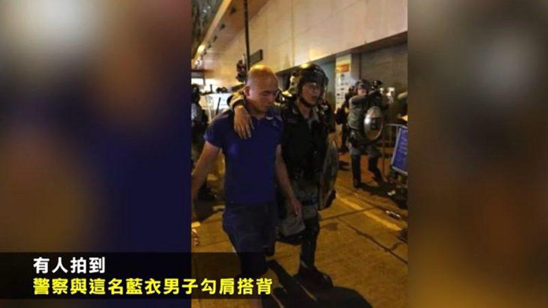 有媒體拍到一名襲擊記者的男子被捕後,有防暴警搭著該男子肩膀,護送他離開現場。(視頻截圖)