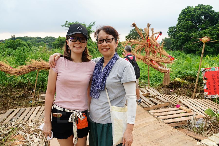 自小在坪輋長大的Janet(右),很支持舞火龍活動,與女兒(左)一齊回來做義工。(陳仲明/大紀元)