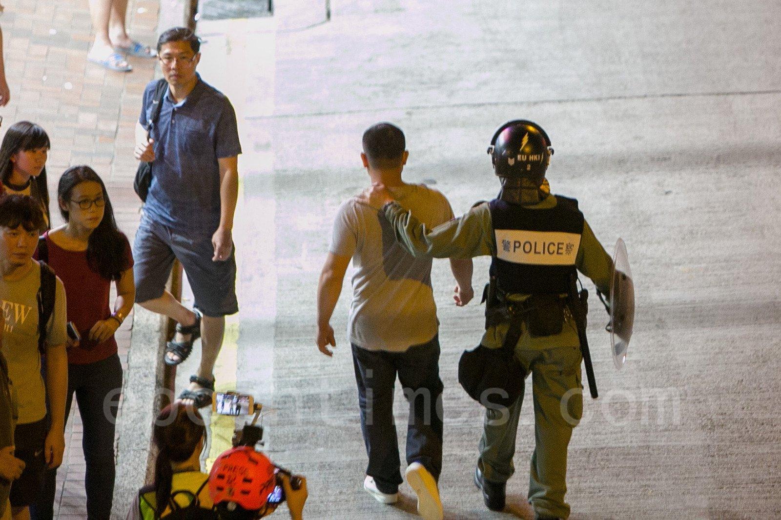 15日晚在北角炮台山,警察護送打人的福建幫成員離開現場。(楊家豪/大紀元)