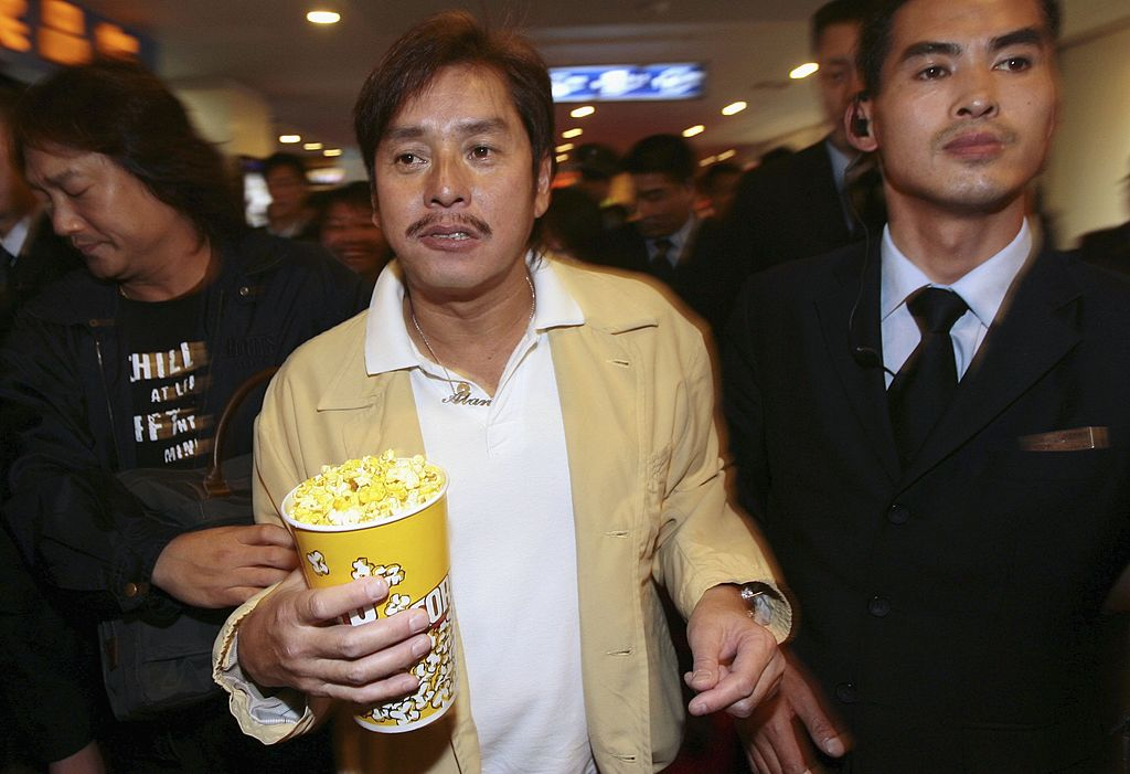香港歌手譚詠麟(中)2006年5月25日在中國江蘇省南京市拿著一杯爆米花,在安保人員簇擁下參加一場新聞發佈會。(China Photos/Getty Images)
