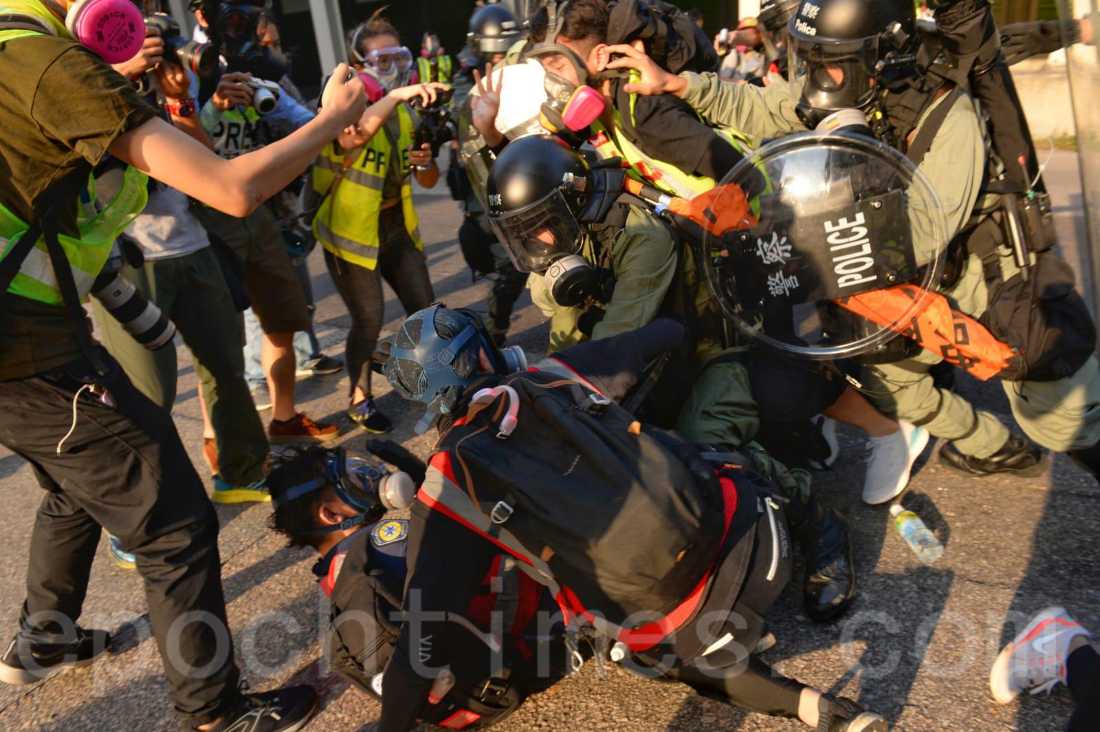 21日「光復屯門公園」遊行中,警察推進時衝撞醫護人員,之後對其搜身。(宋碧龍/大紀元)