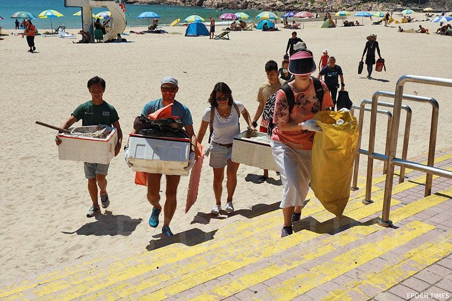 義工們將收集到的垃圾搬運至石澳泳灘旁的垃圾站。(陳仲明/大紀元)