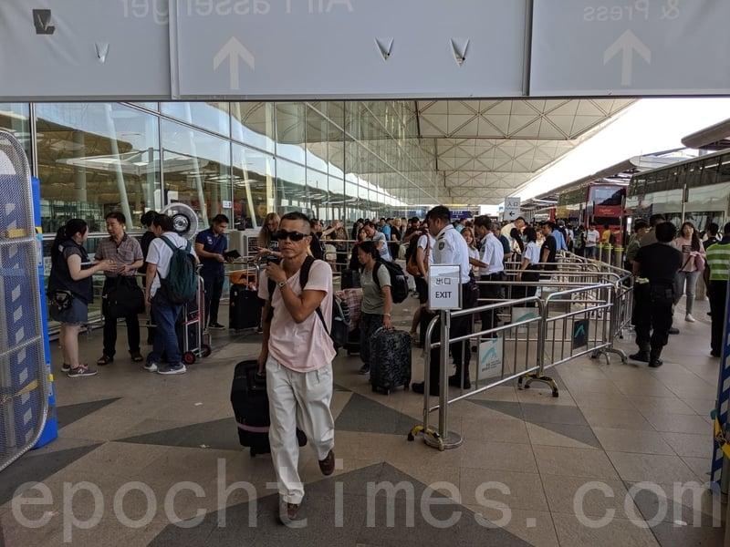 乘客進入機場客運大樓時,需要先接受檢查。(黃曉翔/大紀元)