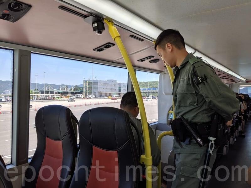 有防暴警察登上巴士,檢查部份乘客身份證和搜身。(黃曉翔/大紀元)