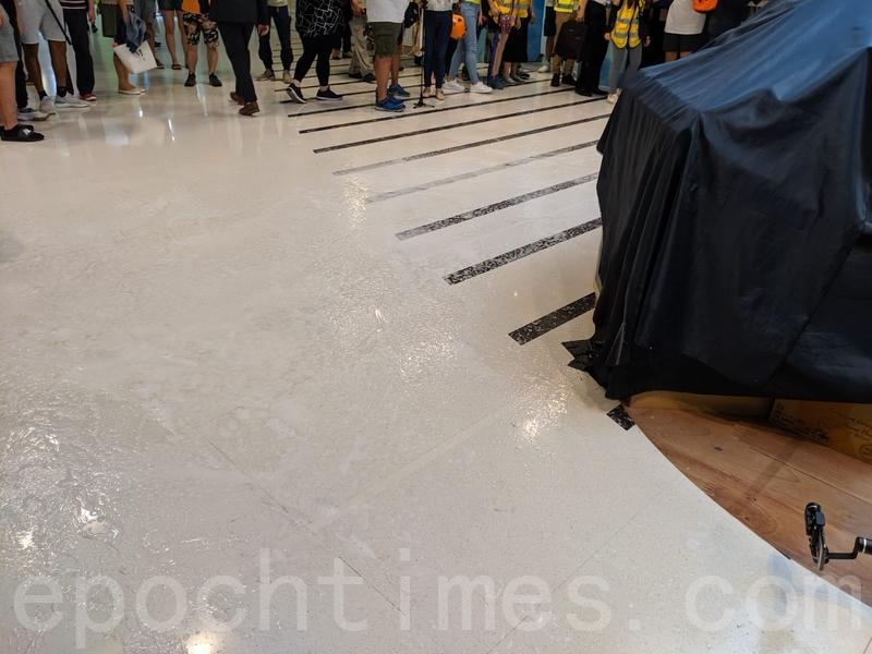 青衣城內,有人在地上倒類似皂液的透明液體。(黃曉翔/大紀元)
