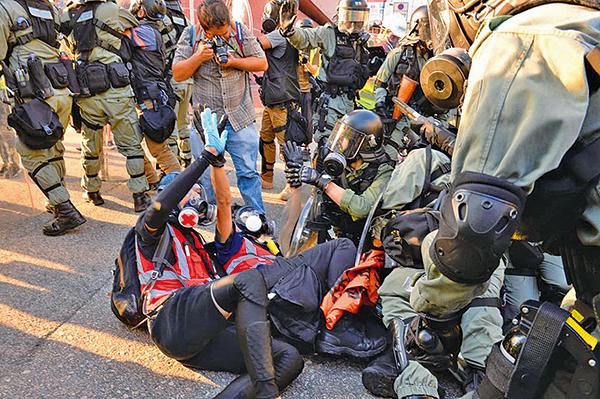 周六屯門遊行期間,警方多次向義務救護員施暴,其中在V City有7名救護員被捕。人權監察發表聲明譴責警方濫捕救護員。(宋碧龍/大紀元)