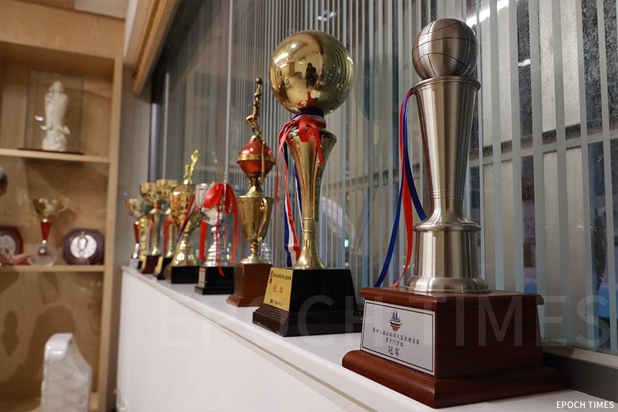 在何樹勛的辦公室裏,擺放著一大排獎盃,這些獎盃都是籃球賽的「戰利品」。(陳仲明/大紀元)