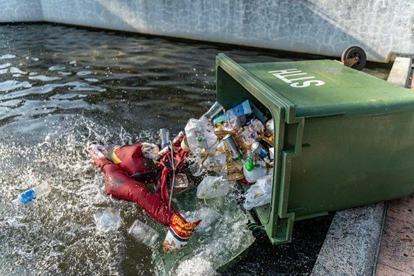 民眾把中共血旗扔進垃圾桶並推入水池。(Anthony Kwan/Getty Images)