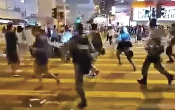 21日晚,警察第一次從警署衝出來把正在在B1對開馬路上過馬路的路人按到地上後帶回警署。(影片截圖)