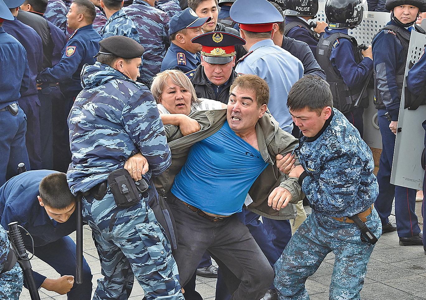 圖為2019年6月9日,努爾蘇丹。哈薩克警察在抗議集會上拘留示威群眾。(AFP)