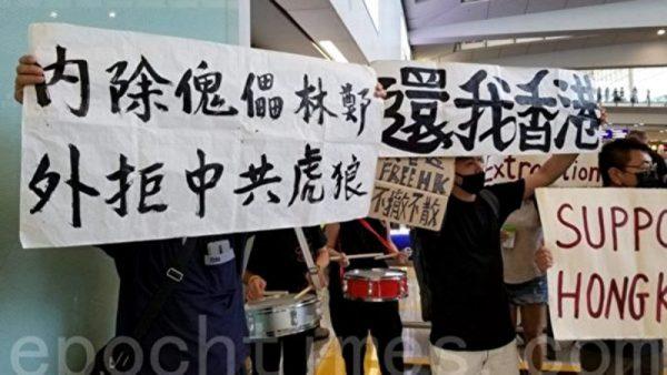 7月26日,香港,一群航空界職員在香港機場的接機大廳舉行集會抗議。圖為抗議人士以「內除傀儡林鄭 外拒中共虎狼」、「還我香港」等橫幅表達心聲。(宋碧龍/大紀元)