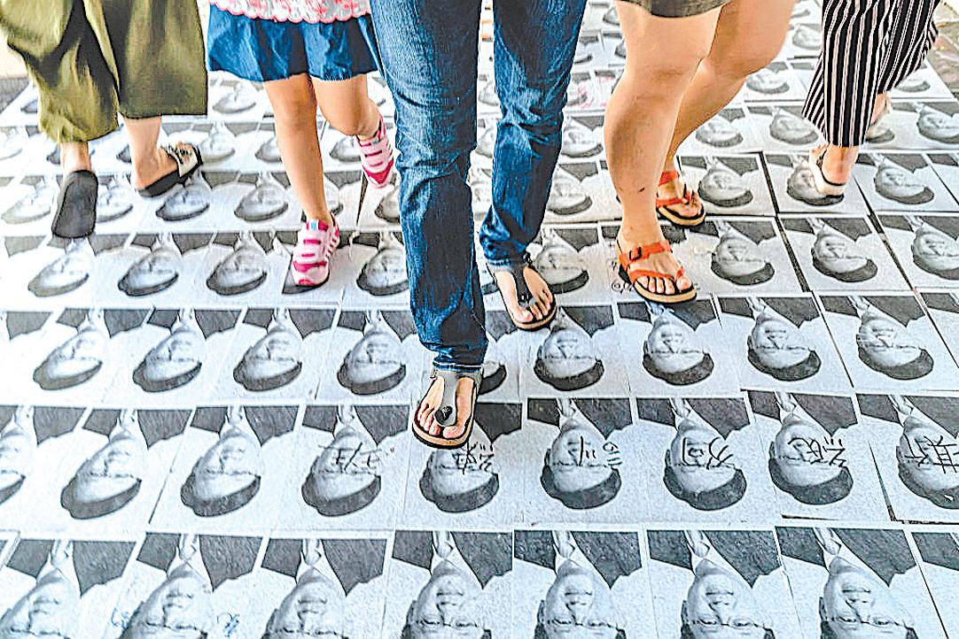 何君堯照片被鋪地上任人踩,成為當地一景。(AFP)
