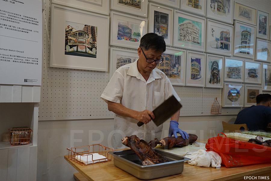 青山道303號畫展開幕儀式上,特別預訂了洪慶海鮮燒臘飯店(洪慶大飯店)的燒豬,負責人李先生前來參與活動。(曾蓮/大紀元)