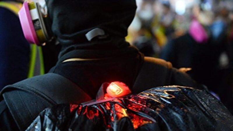 9月21日晚,有黑衣人向警車投擲汽油彈,其中一人背上有臥底警察的閃光燈辨識裝置,被質疑是港警自導自演。(大紀元)