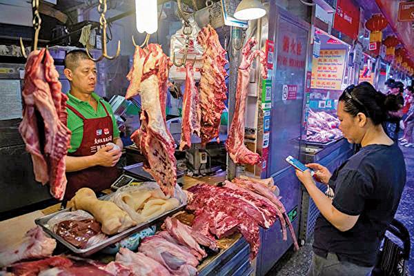 豬肉價格飆漲高達50%,肉類進口應聲增加,造成全球供應緊張,並在各國肉類市場中引發連鎖反應。圖為中國民眾購買豬肉。(Getty Images)