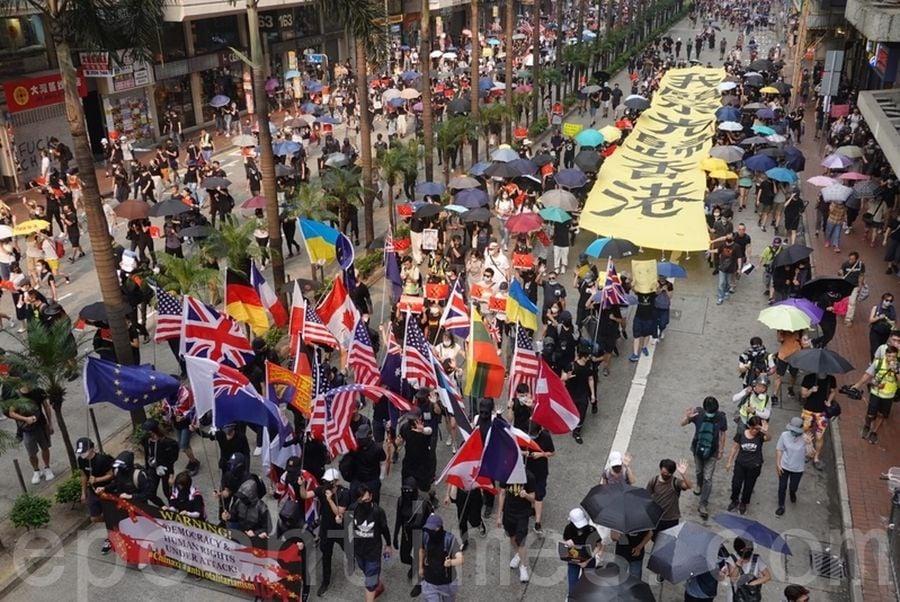 2019年9月29日,全球24個國家、65個城市舉行「全球連線-共抗極權」遊行。香港灣仔遊行隊伍,巨型橫幅經過。(余鋼/大紀元)