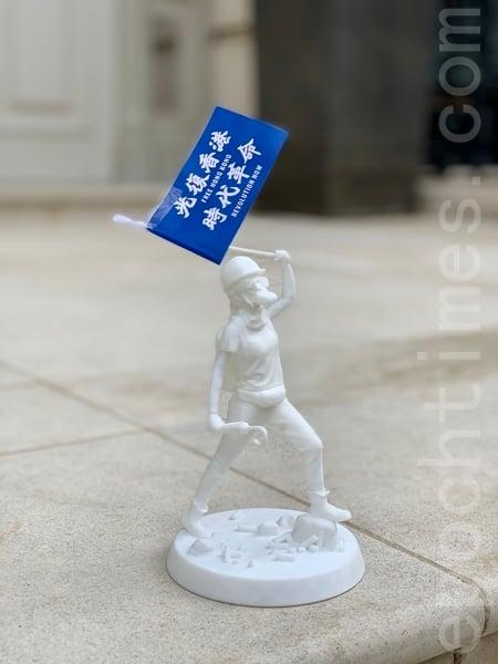 港人攜帶小型新民主女神像參加集會。(唐詩韻/大紀元)