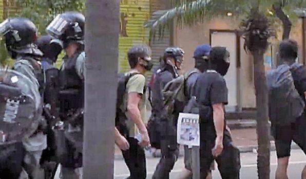 一群示威者被拍到與警方打招呼,更有記者聽到有人說:「自己人」。(余鋼/大紀元)