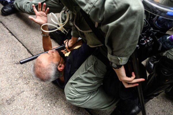 香港警察2019年9月29日在銅鑼灣購物區拘捕抗議者時把一名白髮老人推倒在地並以膝蓋壓制。(PHILIP FONG/AFP/Getty Images)