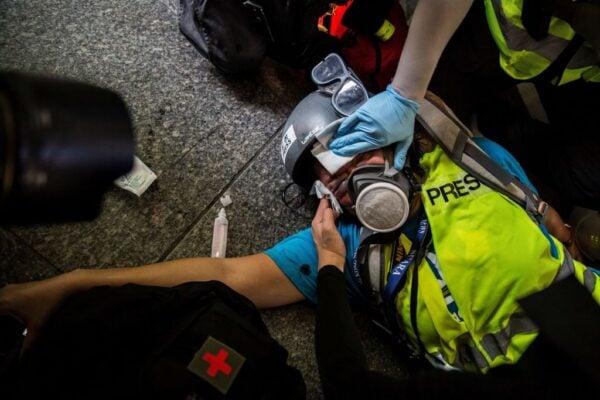 香港9.29反極權活動現場一度爆發力抗議人群與警察的肢體衝突,警方在撤退時曾開槍掩護,期間一名在現場採訪的媒體記者疑似被擊中受傷倒地。有急救人員上前施救。(ISAAC LAWRENCE/AFP/Getty Images)