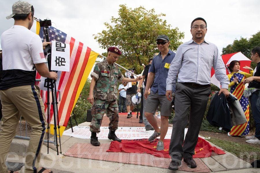 參加集會的民眾踩踏象徵中共的「赤納粹」旗。(林樂予/大紀元)