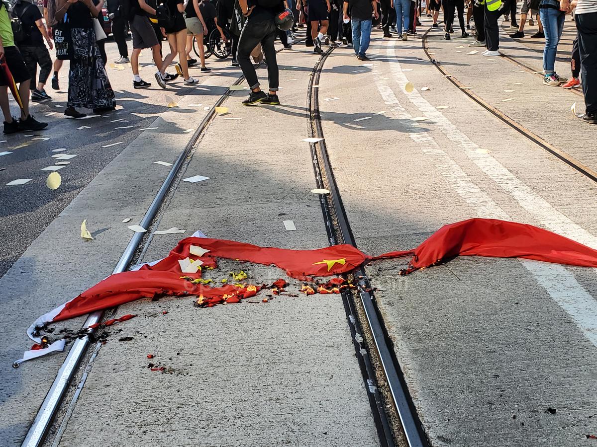 10.1大遊行,香港六區同時發起了「沒有國慶 只有國殤」的集會,在港島附近,市民焚燒了中共血旗。(羅亞/大紀元)