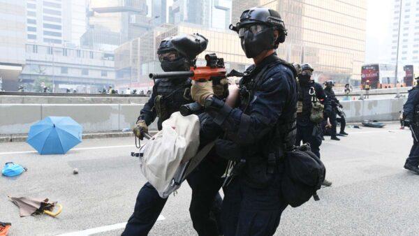 9月29日的暴力鎮壓中,港警將被捕的抗爭者頂在身前,向示威人群方向推進。(MOHD RASFAN/AFP/Getty Images)