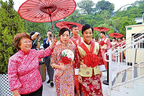 八對夫妻在大妗姐手持紅傘陪同下,在饒宗頤文化館園區內參與「迎親行大運」。