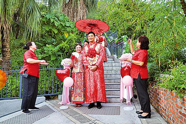 八對夫妻在大妗手持紅傘陪同下,接受灑喜米、喜歌喜樂等祝福。