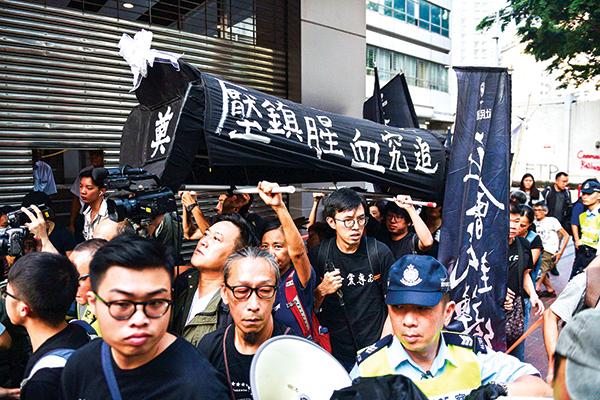 10月1,香港市民紛紛走上街頭示威。有市民舉著的棺材上寫著:追究血腥鎮壓。(Getty Images)