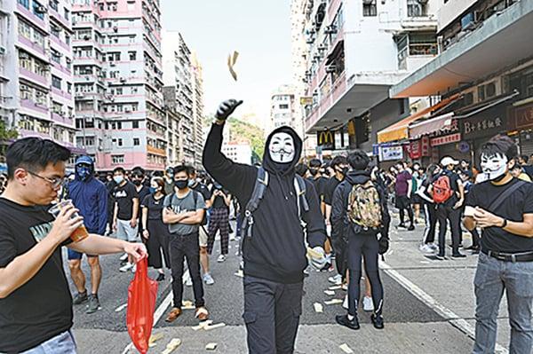 10月1日下午,長沙灣有市民戴上V煞面具,向空中撒溪錢。( 文瀚林/大紀元)