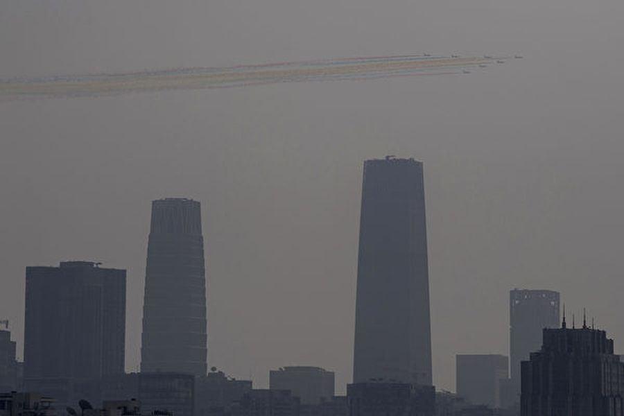 中共十一閱兵日陰霾漫天。彩色飛機群被籠罩在陰霾之中。(NOEL CELIS/AFP)