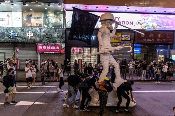抗議民眾將反送中自由女神像推到街上。(Laurel Chor/Getty Images)