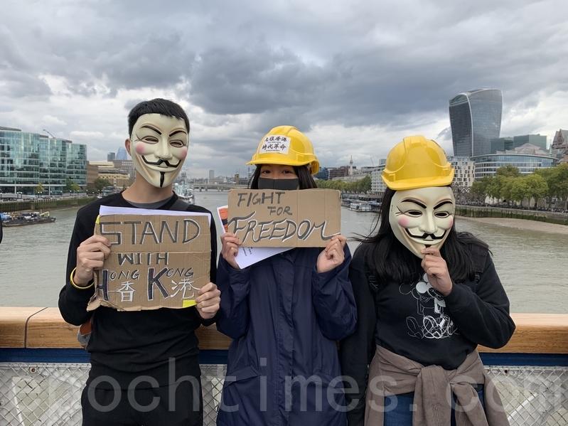 10月5日,反禁蒙面法生效的首天,數百名在英港人於著名地標倫敦塔穚(Tower Bridge)上築起人鏈。港人帶上面具、頭盔,手持標語在倫敦塔穚上抗議港府漠視民意。(唐詩韻/大紀元)
