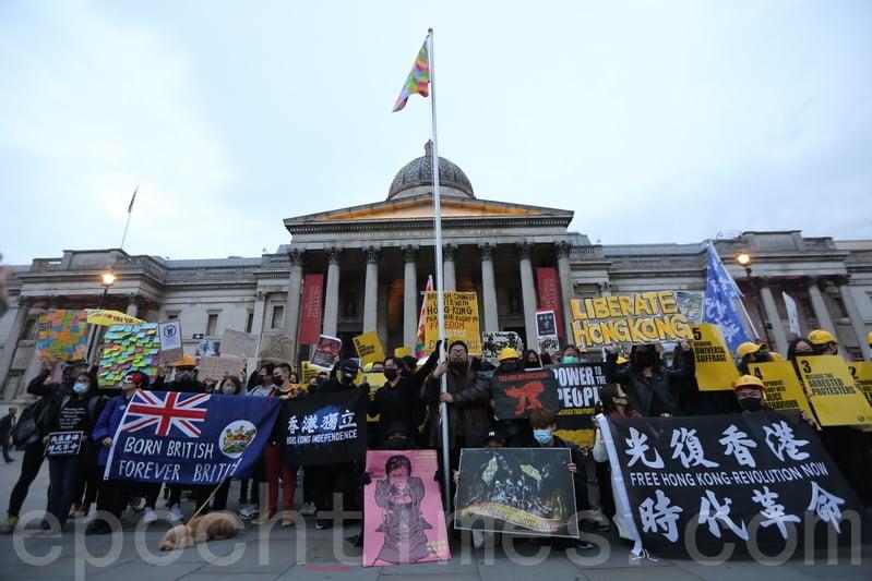 10月5日,巴丟草及參加集會的港人在特拉法加廣場啟動「連儂旗」升旗儀式。幟旗在港人伴唱《願榮光歸香港》的歌聲下飄升在倫敦的天空中,場面令人感動。(唐詩韻/大紀元)