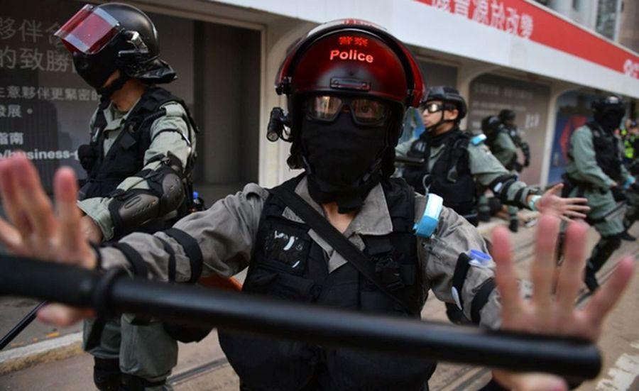 一群香港警察2019年10月5日在港島中區追捕一對戴著口罩上街抗議的夫婦後,一名香港警察試圖封鎖該地區,阻擋媒體記者上前採訪。(NICOLAS ASFOURI/AFP via Getty Images)