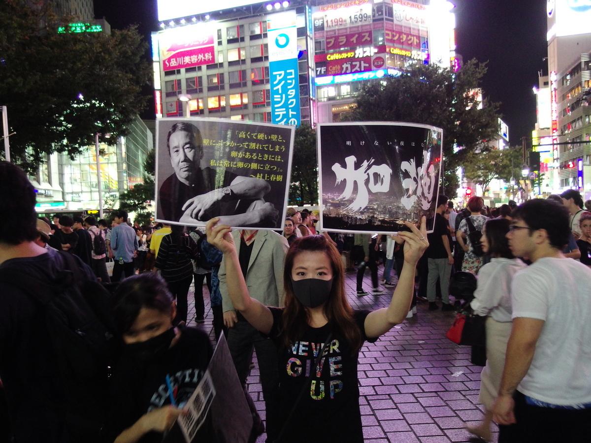 向日本人展示,日本作家村上春樹的名言,「假如這裡有堅固的高牆和撞牆破碎的雞蛋,我總是站在雞蛋一邊。」表達對香港抗爭者的支持。(張本真/大紀元)