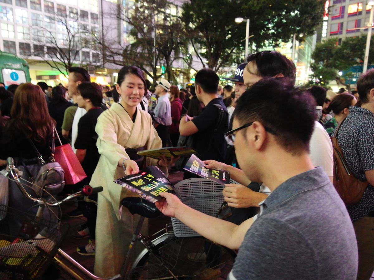 有支援港人的日本民眾在派發「與香港同行」單張及「願榮光歸香港」的歌詞。(張本真/大紀元)