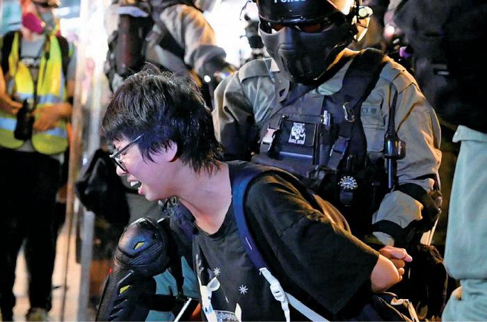 警方昨晚在旺角的行動中,拘捕兩個全無裝備的年輕人,其中一人被警員以胡椒噴劑噴面,表情痛苦。(文瀚林/大紀元)