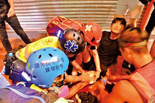 10月4日,便衣警在元朗開槍打傷學生。圖為事發當晚, 被槍傷的14歲少年在現場接受護理。(余天佑/大紀元)