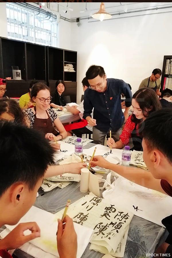 黃憬珩近日參與香港科技大學外國學生在鯉魚門創意館舉辦的文化工作坊,將同學英文名翻譯為中文,教他們寫書法,推廣中國書畫文化。(受訪者提供)