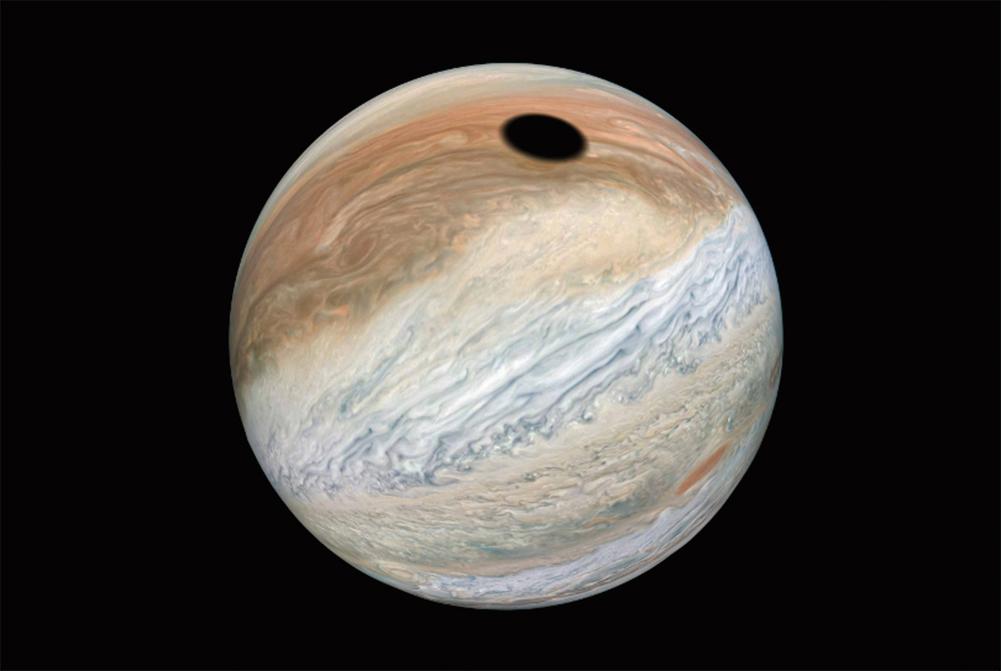 照片顯示在木星洶湧翻騰的雲層上有一塊巨大的黑斑。分析發現,這原來是木衛一在木星上投下的巨大陰影。(NASA/JPL-Caltech/SwRI/MSSS/Kevin M. Gill)