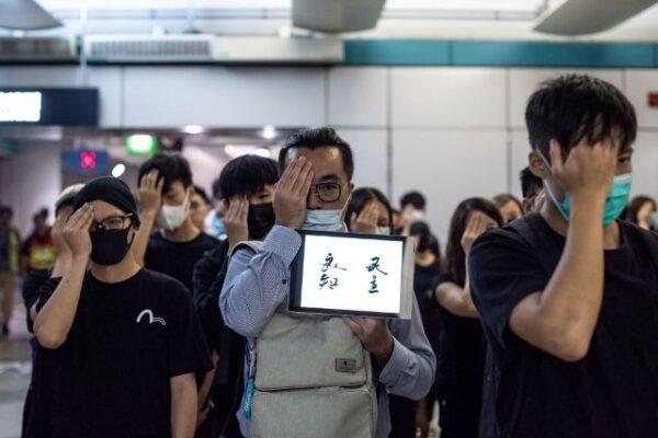 香港抗議民眾2019年8月21日在香港元朗地鐵站舉行的無聲集會上遮住右眼,以此抗議香港警方濫用武力打傷一名女子的右眼以及縱容幫派分子襲擊市民。(PHILIP FONG/AFP/Getty Images)
