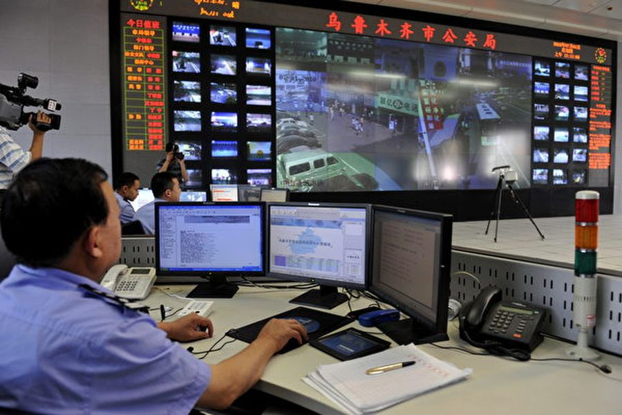 10月7日,美國商務部將28個涉及在新疆打壓少數民族的中共公安機構和公司列入貿易黑名單。圖為中共公安正在監視新疆烏魯木齊居民。 (AFP/Getty Images)