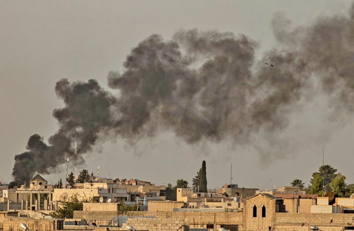 10月9日,土耳其向敘利亞東北部開火,圖為邊境城市Ras al-Ain 被轟炸,濃煙滾滾,平民倉皇奔逃。(Getty Images