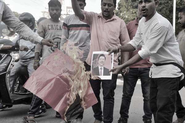 習近平訪問印度,場內在歡迎,場外印度人則在焚燒中共血旗和畫像以示抗議。(BIJU BORO/AFP via Getty Images)