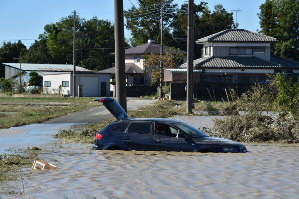 2019年10月13日,受到颱風海貝思影響,多條河川氾濫。圖為汽車版發現泡在田里的洪水中。(KAZUHIRO NOGI/AFP via Getty Images)