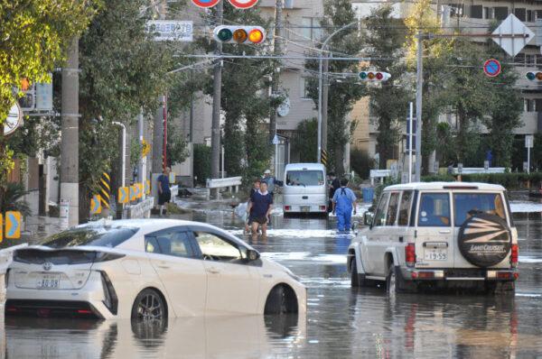 2019年10月13日,在川崎的颱風海貝思災後,當地居民清理被洪水淹沒的街道。(JIJI PRESS/JIJI PRESS/AFP via Getty Images)