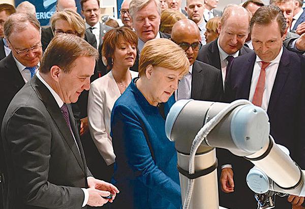 特朗普宣佈支持美國5G發展,並暗示未來可能發展6G。圖為今年4月漢諾威博覽會上,德國總理和瑞典首相在查看愛立信的5G卡。(Getty Imges)